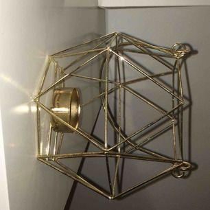 En ljusstake i guld. Köparen står för frakt.