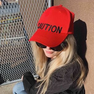 """Röd keps med texten """"Caution"""" framtill"""