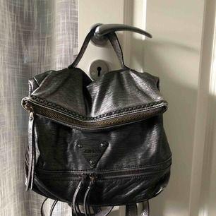 Äkta Guess väska i ormskinns likn mjukt material. Handväska, axelremsväska & ryggsäck i ett. Remmar finns till allt. Dragkedjan kan öppnas, väskan blir större. Bild på innerfodret på en sida. Köpt i Guess butik i USA. Anv. ca 5 ggr!  Kan skicka spårbart.