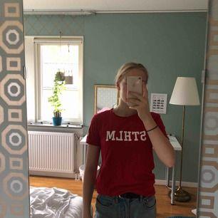 Röd tröja från Lager 157 med texten Sthlm på bröstet. Möts i Sthlm eller så tillkommer frakt