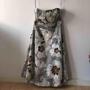 Strapless blommig klänning från Kappahl. Överdelen av klänning har benign inuti vilket ger klänningen form. Bara använd ett par gånger, i perfekt skick.