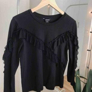 """Svart långärmad t-shirt med """"spetsvolangdetalj"""" inköpt på Monki."""