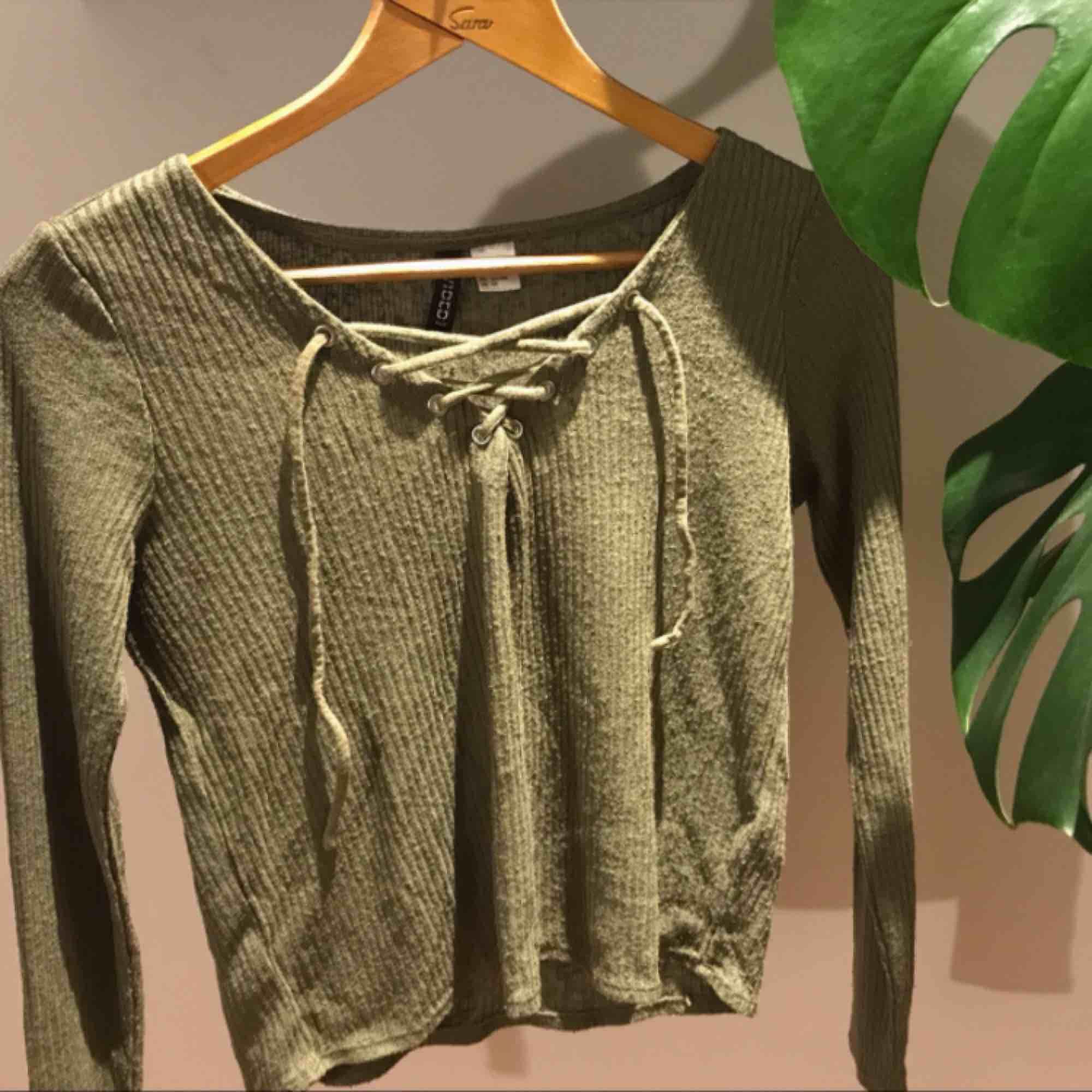 Långärmad militärgrön tröja med snören. Mjuk och bekväm och perfekt nu till hösten! Säljs pga att den inte kommer till användning. Frakt tillkommer.. Toppar.
