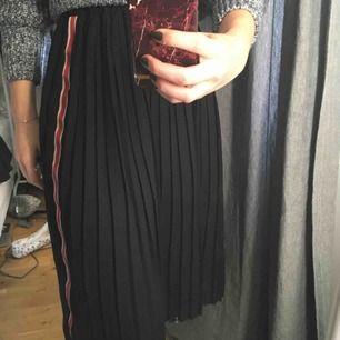 En längre kjol från zara. Använd några gånger men är i fint skick. Kjolen är svart men har vit/röd linje på både höger & vänster sida.