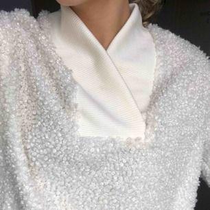 Krämvit/benvit mysig tröja med en krage.