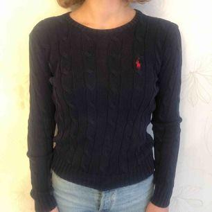 Ralph Laurent kabel stickade tröja i marin blå med röd logga, använd 1 gång. Säljer pga inte nån användning. Tröjan är som ny och har ingen skada. Kan mötas upp i centrala Stockholm annars står köparen för frakt