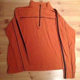 Orange sportig vintage i använt skick, en liten fläck (se bild). Svarta sidenränder på sidan.