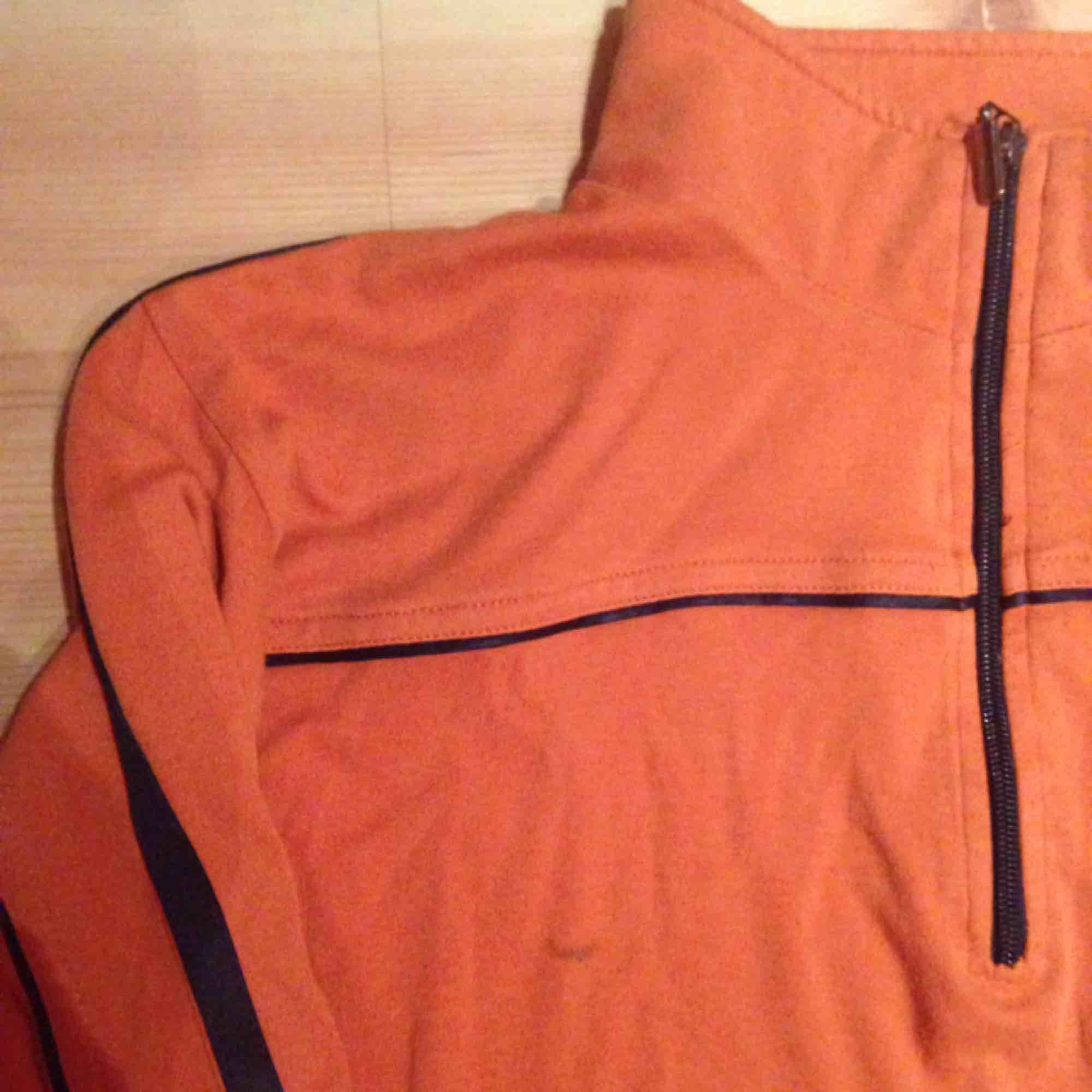 Orange sportig vintage i använt skick, en liten fläck (se bild). Svarta sidenränder på sidan. . Huvtröjor & Träningströjor.