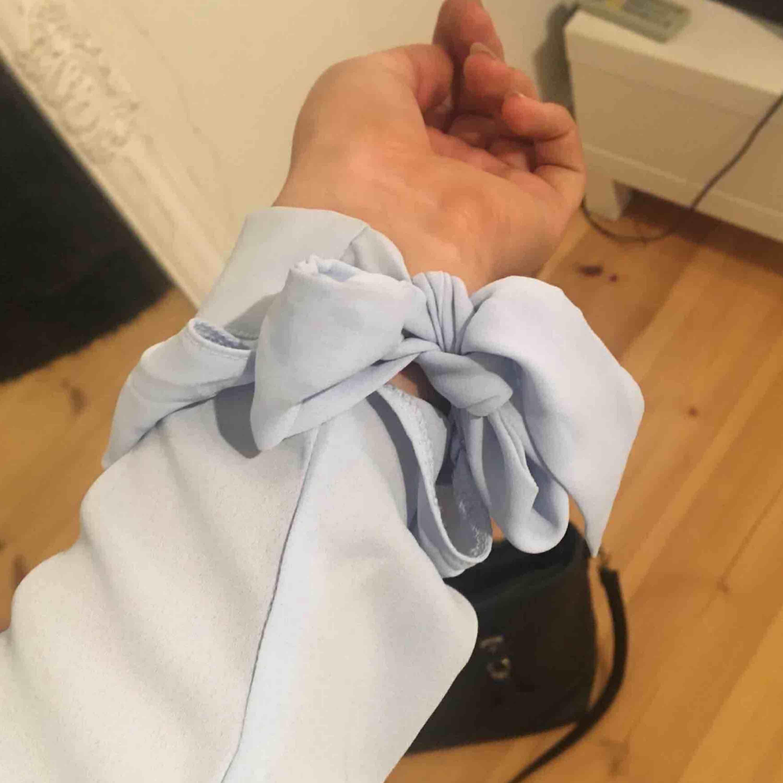 Suuupersöt och fin blå blus med rosetter på handlederna och i ryggen! . Blusar.
