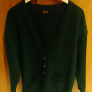 A dark green cardigan with golden buttons and black outlines. Very nice quality and is used a few times. No holes that I know of. 85% acrylic