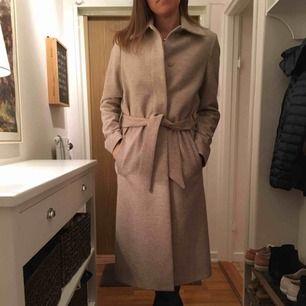 """Superfin beige kappa """"Iza Long Wool Coat"""" från Filippa K. Inköpt på Design Only.  Prisetikett inkl extra knapp finns. Ordinarie pris 4099 kr, använd endast ett fåtal gånger. Vid intresse finns fler bilder på Naked's hemsida där den säljs just nu."""