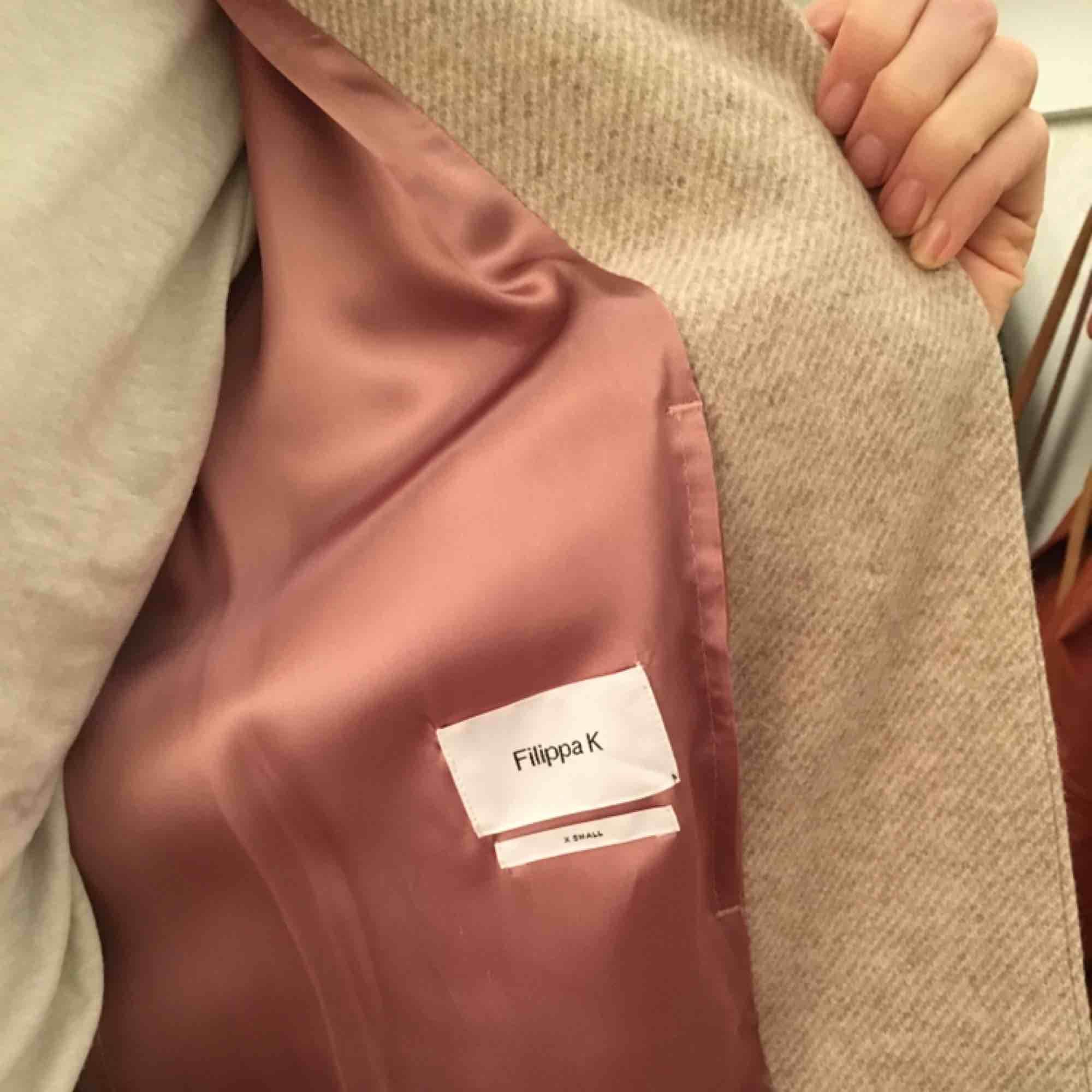 """Superfin beige kappa """"Iza Long Wool Coat"""" från Filippa K. Inköpt på Design Only.  Prisetikett inkl extra knapp finns. Ordinarie pris 4099 kr, använd endast ett fåtal gånger. Vid intresse finns fler bilder på Naked's hemsida där den säljs just nu.. Jackor."""