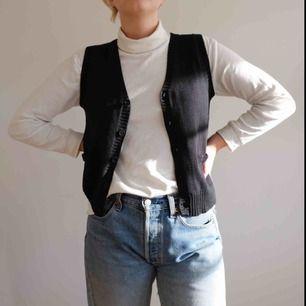 Svart stickad väst i storlek S. Supersnygg att ha över tröjor eller bara för sig själv!