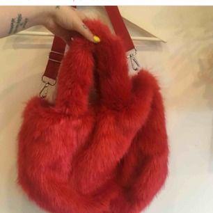 Ganska stor väska i röd fuskpäls från Monki. Använd bara ett par ggr, i nyskick.