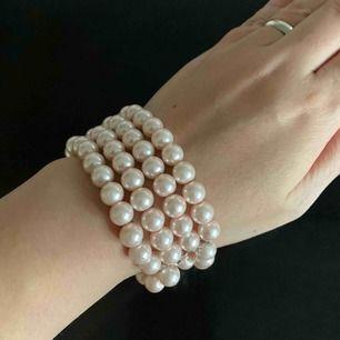 Oanvänd armband i rosa pärlor.