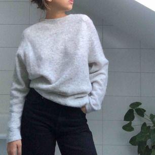 En grå stickad tröja från vila. Man kan ha snörningen framtill eller baktill (personligen tycker jag att det är snyggare baktill).