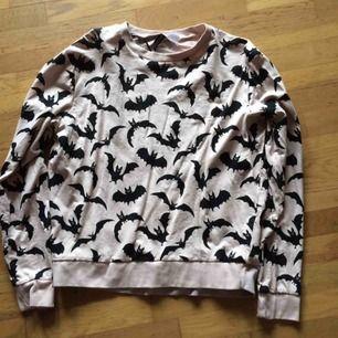 Ljusrosa sweatshirt med fladdermusprint i storlek M. Sparsamt använd så i fint skick, har legat nerpackad så därav att den är skrynklig. Priset är inkl frakt :)