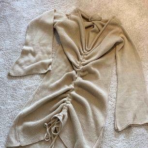 Stickad klänning i nude färg med scrunch fram!   Man kan justera den som man vill! Aldrig använd, endast provad. Strl 44 men passar mig som är 36/38 också, bara lite stor kring axelpartiet så den blir off shoulder