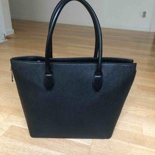 En svart handväska med guldiga detaljer. Denna är andvänd max två gånger, så gott som ny helt enkelt!! Köpt för 350 kr.