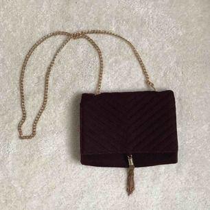 Röd väska i velvet-material, liten ficka med dragkedja på insidan.