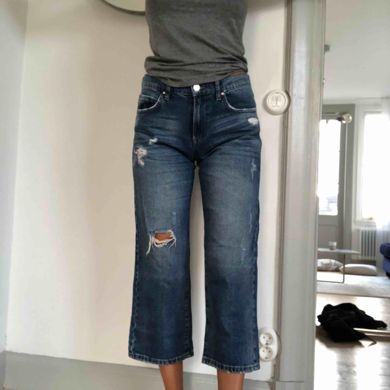 Croppad jeans från Bikbok med slitningar. Aldrig använda. 100% bomull . Jeans & Byxor.