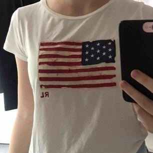 Säljer en fin vit Ralph Lauren t-shirt med en amerikansk flagga på bröstet. Tröjan är i normalt skick och är i storlek XL (BARNSTORLEK) men skulle säga att den passar en XS/S. Köparen står för frakten !