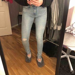 ett par super sköna högmidjade blåa jeans med en slitning på knät i storlek S.