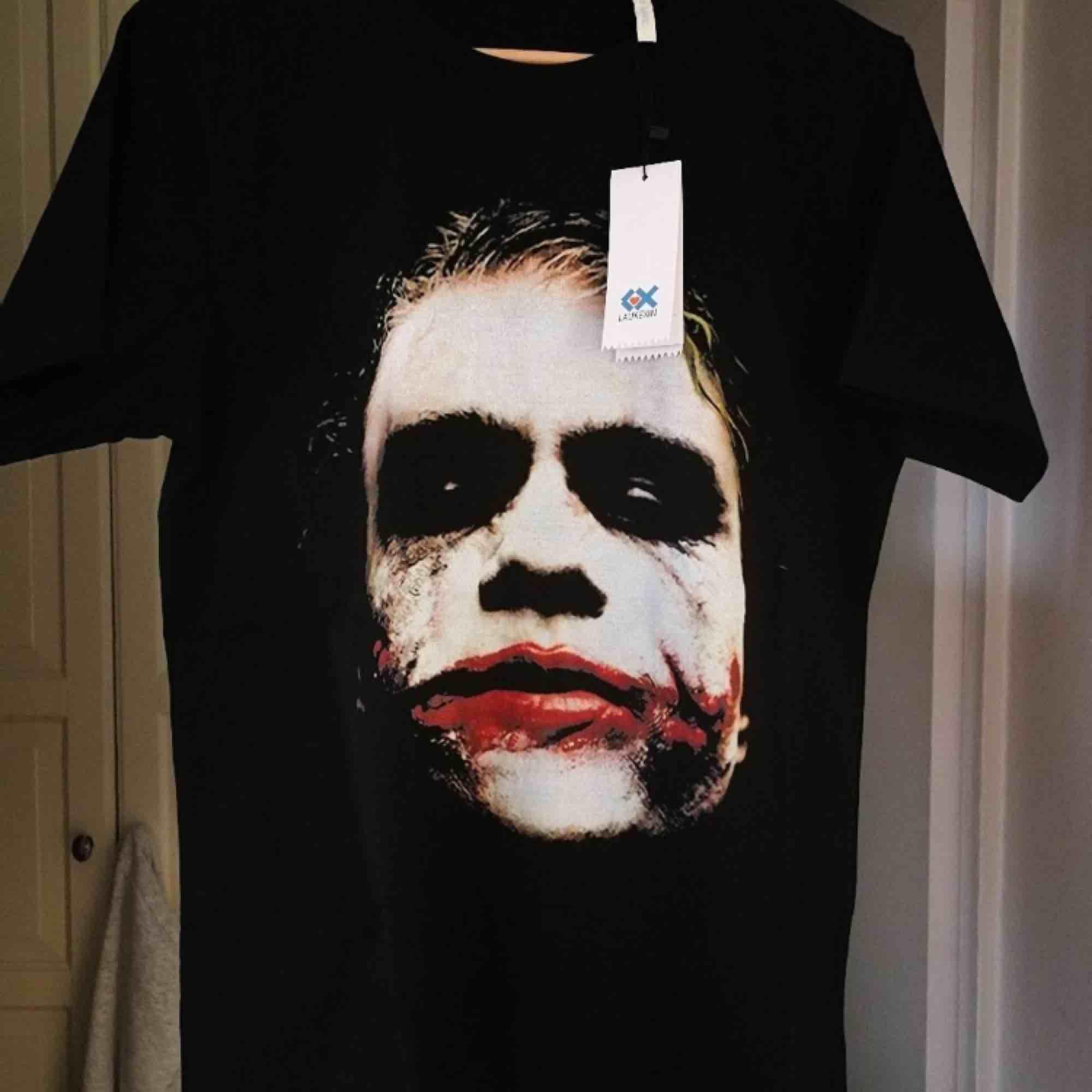 Oanvänd t-shirt av skön och tjock bomull, med avbilden på Jokern från Batman.. T-shirts.