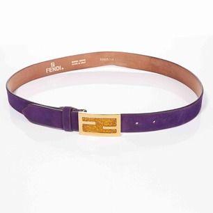 Vintage Fendi logo skärp i ametist lila mocka. Spännet är i guldmetall med saffransfärgat glitter. Skärpet är i fint skick med endast några få slitningar (se bilder)  Längd: 83-93 cm Bredd: 3 cm