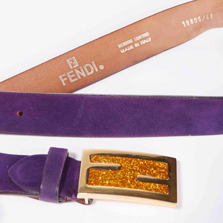 Vintage Fendi logo skärp i ametist lila mocka. Spännet är i guldmetall med saffransfärgat glitter. Skärpet är i fint skick med endast några få slitningar (se bilder)  Längd: 83-93 cm Bredd: 3 cm. Accessoarer.