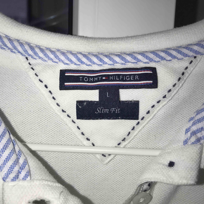 Vit Tommy Hilfiger Piké, Storlek L (små i storlekar), Använd fåtal gånger, nypris 600kr, köparen står för frakt. T-shirts.