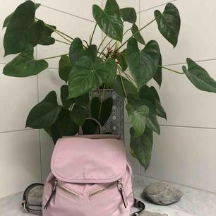 En skitsnygg pastellrosa ryggsäck från Parfois med många smarta fack och fickor. Får plats med mycket men ändå en liten väska.