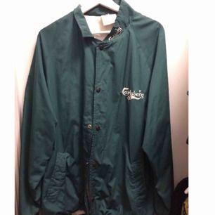 Oversize jacka, grön, broderat carlsberglogga bak & fram. Köpt på Emmaus, använd fåtal ggr.