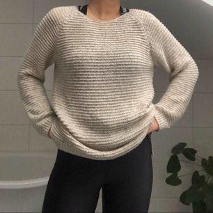 """En stickad tröja med """"hålmönster"""" på baksidan. Lite längre baktill för att täcka rumpan. Skönt och mysigt material i en sand/beige färg!"""