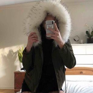 Militärgrön Faux fur jacket, med fluffig luva och insida. Använd ett fåtal gånger, funkar till både vinter och höst. Snörning vid midjan för en tydligare siluett.