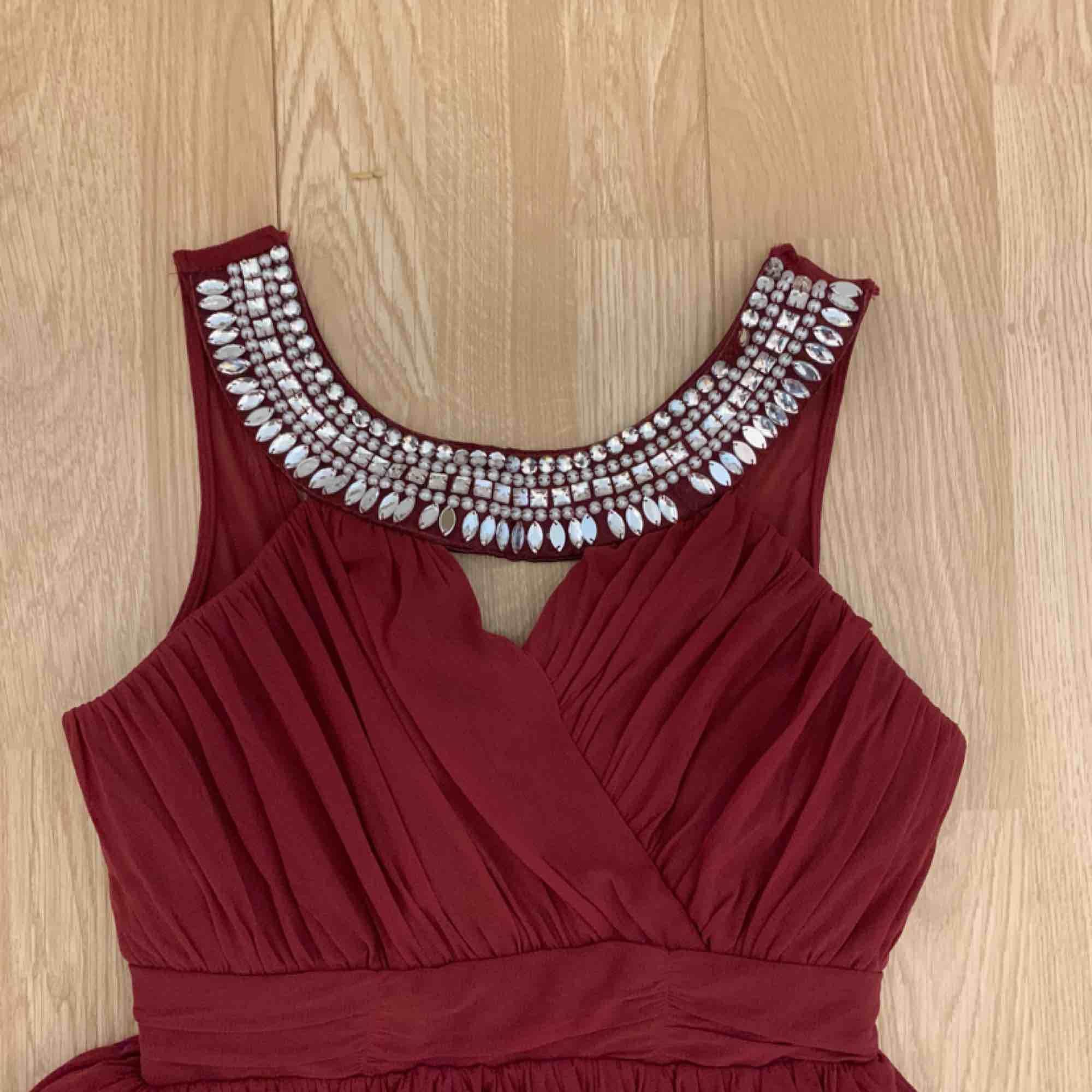 Vinröd kort klänning från Elise Ryan storlek 38.  Fint skick förutom att 2 stenar från framsidan är borta.  Frakt kostar 63kr extra, postar med videobevis/bildbevis. Jag garanterar en snabb pålitlig affär!✨ ✖️Fraktar endast✖️. Klänningar.