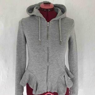 Väldigt fin grå zip hoodie med volang kant längst ner, fint skick, använd 2/3 gånger! Du står för frakt😊
