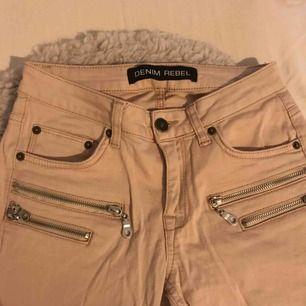 Rosa- beige byxor med låg midja. Har dragkedjor som detaljer, även nere vid byxorna. Köparen står för frakten och betalningen sker via Swish👍