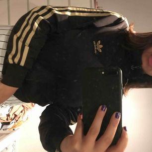 En Adidas kofta med guldiga sträck