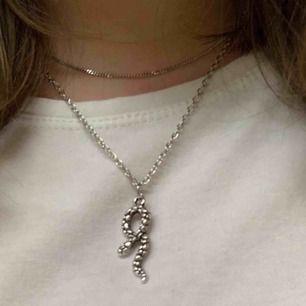 Ett silvrigt halsband med en orm på, säljer då jag inte använder🌎frakt ingår
