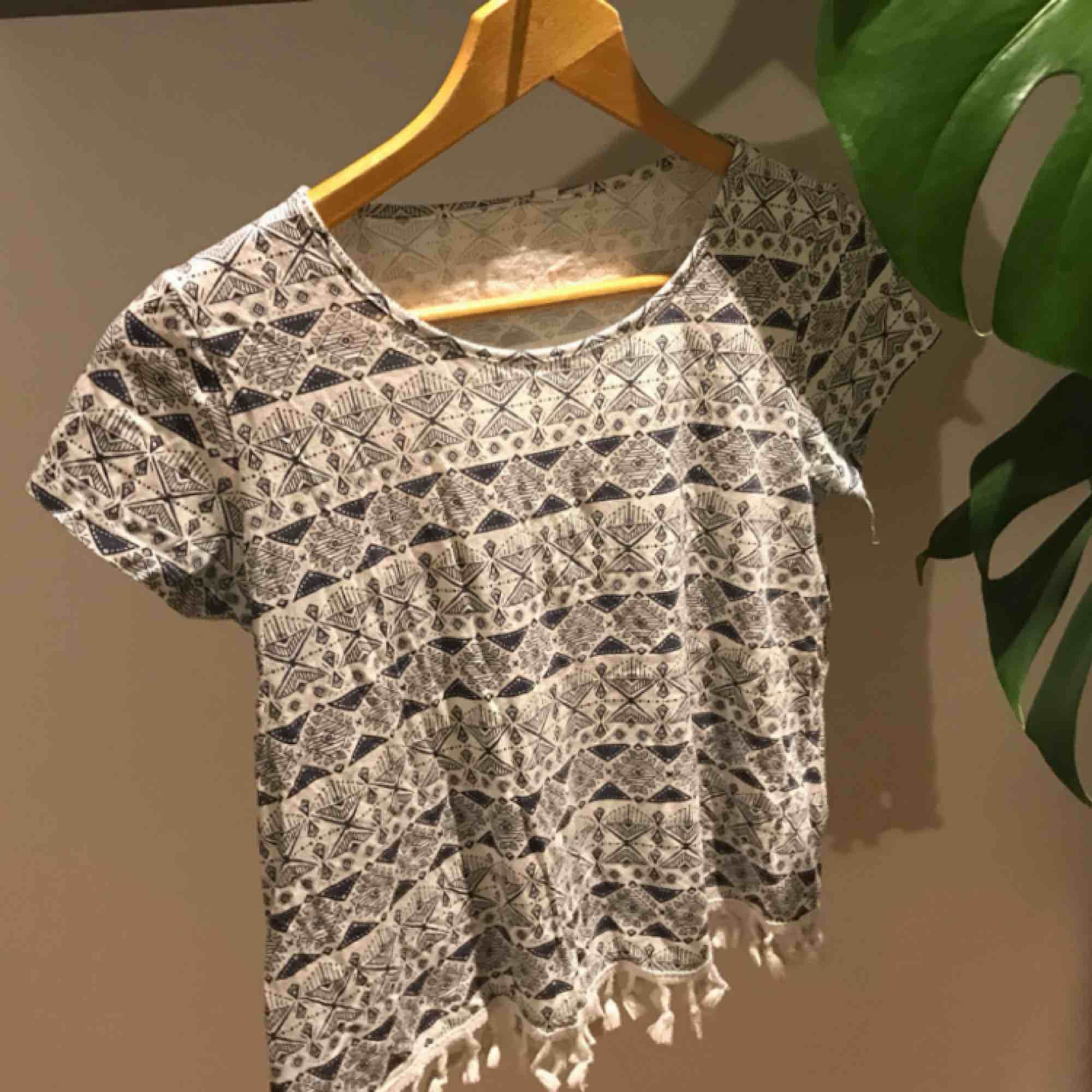 T-shirt med små söta tasslar längst nere. Mer en S än en XsS. Inköpt flera år sedan och knappast använd. Vit med mörkblått fint mönster. Frakt tillkommer!. T-shirts.