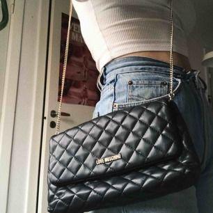 Äkta Love Moschino-väska, köptes för 2 år sedan. Väskan är i fint skick men har en liten slitning vid knäppet, inget som riktigt syns. Frakt ingår.