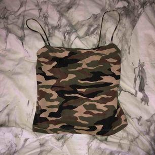 Ett linne med spaghettiband i militärmönster i storlek S från Gina tricot.