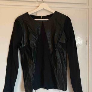 Svart tröja med skinndetaljer och dragkedja i ryggen. Från .object strl M
