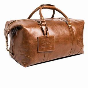 Bredd: 30 cm Höjd: 25 cm Längd: 50 cm Luggage tag läder - Brun Medföljer en axelrem undersidan har tassar av metall för att skydda mot väta och slitage.