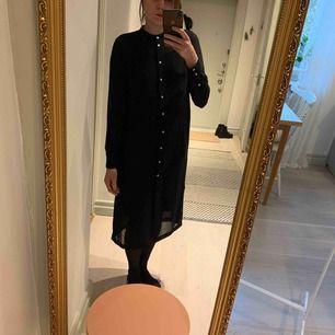 Genomskinlig klänning med pärlemoaktiga knappar