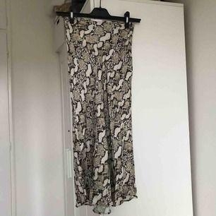 Supersnygg ormskinnsmönstrad kjol från h&m! Använd 2 gånger, så i fint skick! Går nedanför knäna, alltså midilängd❤️❤️Passar xs-m beroende på hur man vill att den ska sitta. Frakt ingår!!🥰😘🤭🥵