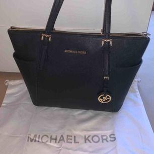Äkta svart handväska från Michael Kors med gulddetaljer, dustbag medkommer och lappar finns även kvar. Mycket använd men i nyskick, därav priset. Nypris ca: 3000kr 🧚🏼♀️🧚🏼♀️bredd: 28cm, höjd: 26cm, djup: 11cm, armband: 23cm. Priset kan diskuteras☺️