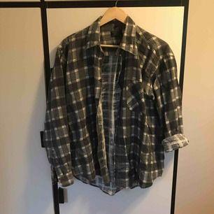 Bomullsskjorta med mörkgrönt/grått rutigt mönster. Mjuk och bekväm. Ursprungligen köpt på UO tror jag men inte säker, nypris ca. 400. Pyttelite sliten men hel och bara använts ett par gånger.