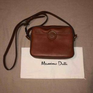 Oanvänd Massimo Dutti axelremsväska i genuint brunt läder. Väskan har guldiga och bruna detaljer med en insida som rymmer mycket. Dustbag och fin inslagning från Massimo Dutti tillkommer. Kan frakta och mötas upp inom stockholm. Priset kan diskuteras!